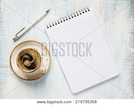 Black coffee with crema in porcelain cup checkered notepad and pencil on a light wooden background; top view flat lay; overhead view