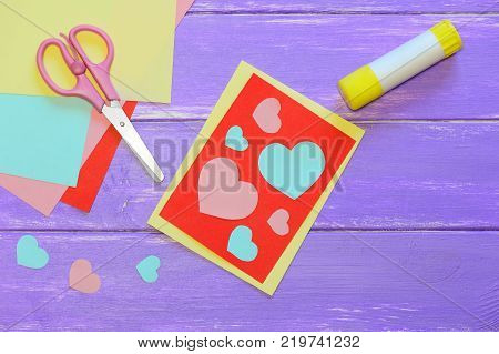 Cute Valentines day card made from colored paper. Scissirs, glue stick, colored paper sheets on a wooden table. Valentines day paper crafts for kids. Top view