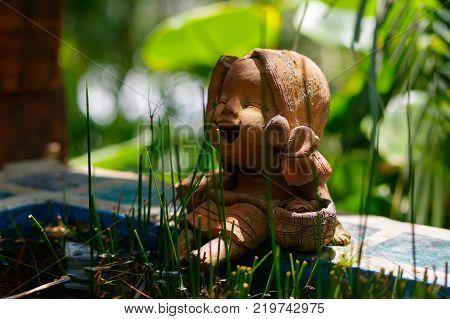Little laughing buddha betwin grass in a garden