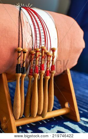 Making bobbin lace in traditional way. Detail on a pillow in a wooden frame and bobbins with wound thread. Pillow lace.