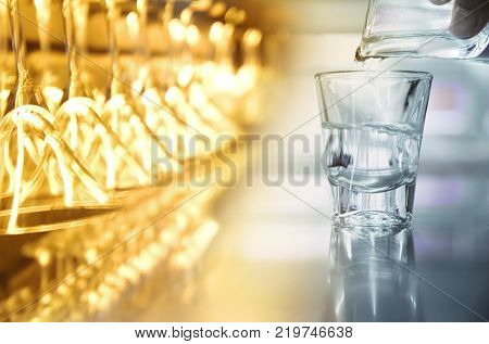 hanging cocktail party glass in orange light with alcohol shot glass with drink liquor in club or bar background
