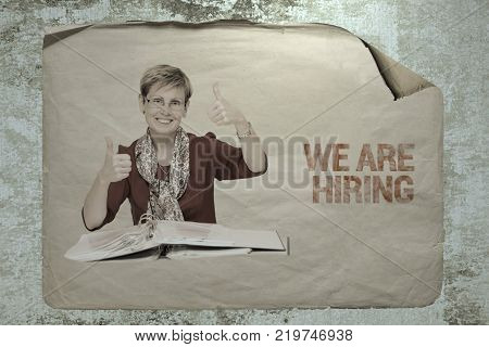old paper job ad on a cement wall with a portrait of a staff member showing ok signs by her hands. busines recruitment concept.