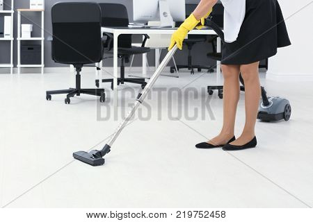 Charwoman hoovering floor in office with vacuum cleaner
