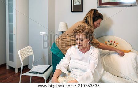 Female caregiver accommodating the pillow to elderly female patient