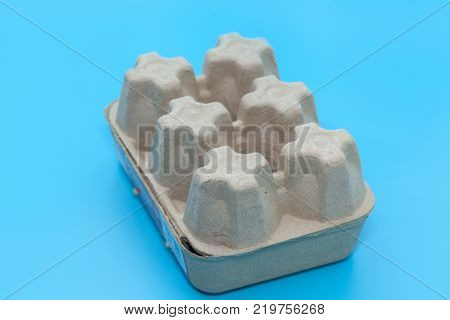 empty paper egg tray box on blue background