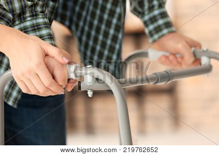 Senior man with walking frame and young caregiver, indoors