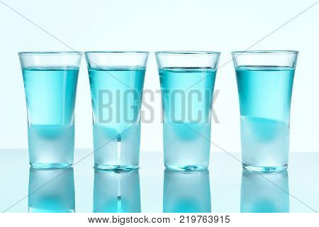 Vodka glass with ice on blue studio background