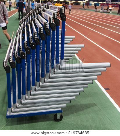 Blue and white hurdles stacked up next to the hurdle straighaway on a cart with wheels are ready to be put on to the indoor track in a track and field indoor arena.