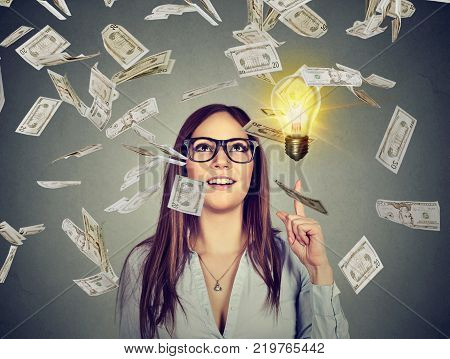 Portrait happy woman in glasses has a successful idea under money rain isolated on gray wall background with bright light bulb above head