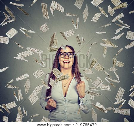 Portrait happy woman in glasses exults pumping fists celebrates success under money rain falling down dollar bills banknotes isolated on gray wall background