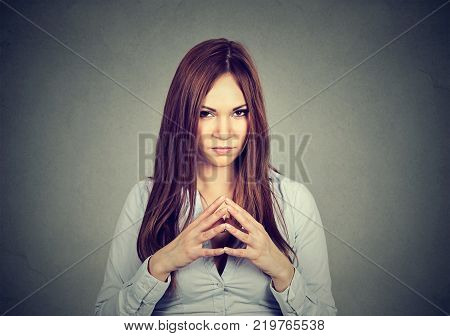 Closeup portrait of sneaky sly scheming young woman plotting something isolated on gray background. Negative human emotions facial expressions feelings attitude