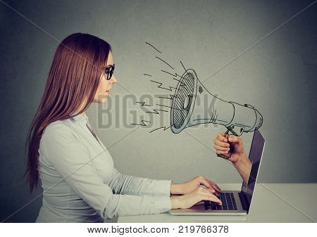 Side profile young woman in glasses sitting at table using working on a computer with megaphone poking out from a laptop screen