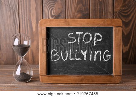 Chalkboard with text STOP BULLYING and hourglass on wooden background