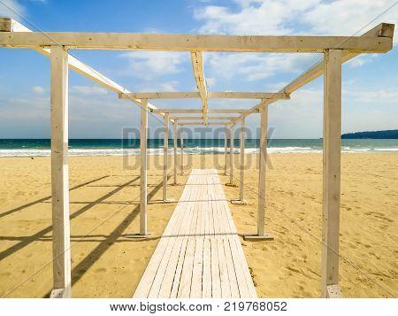 Wooden boardwalk to the sea on a sandy beach. Coast of the Black Sea. South Beach, Varna, Bulgaria