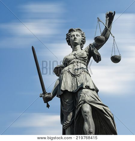 The Statue of Justice - lady justice or Iustitia / Justitia the Roman goddess of Justice against sky. ideal for websites and magazines layouts