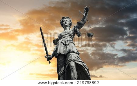 The Statue of Justice - lady justice or Iustitia / Justitia the Roman goddess of Justice against dramtic cloudy sunset sky. ideal for websites and magazines layouts