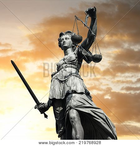 The Statue of Justice - lady justice or Iustitia / Justitia the Roman goddess of Justice against cloudy sunset sky. ideal for websites and magazines layouts