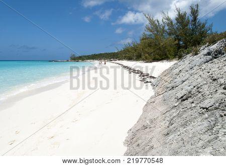 Tourists strolling along the beach on otherwise uninhabited island Half Moon Cay (Bahamas).