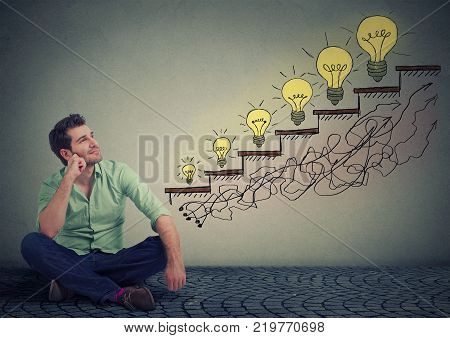 Happy man sitting on a floor in his office dreaming of business education success promotion company growth isolated gray wall texture background. Handsome guy looking up at growing up light bulbs