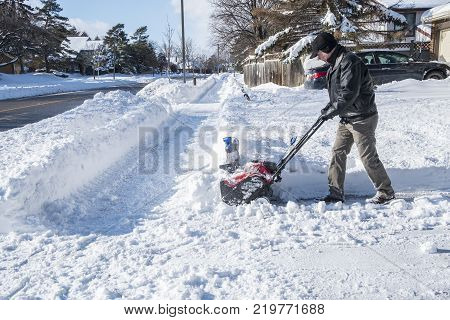 Man Removing Snow with a Snowblower on a Sunny Day