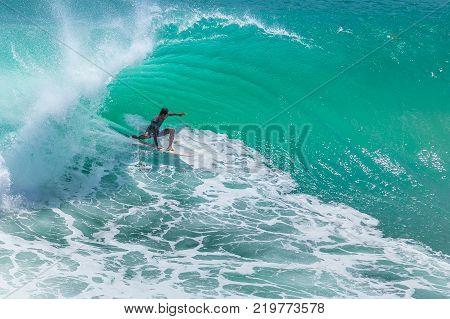 Local surfer riding big green wave at Padang Padang beach, Bali, Indonesia