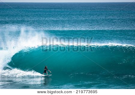 Surfer riding big green wave at Padang Padang beach, Bali, Indonesia