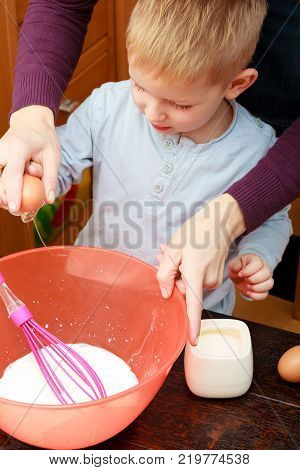 Healthy diet for children youngsters cooking concept. Little kid boy and his mother cooking making cake in bowl