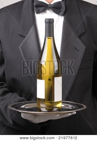 Close up of a Waiter holding chardonnay wine bottle on silver tray vertical format torso only