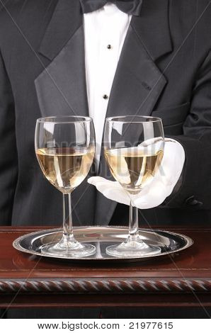 Close up of a Waiter With Two Glasses of Chardonnay on a silver tray and fancy wood table vertical format