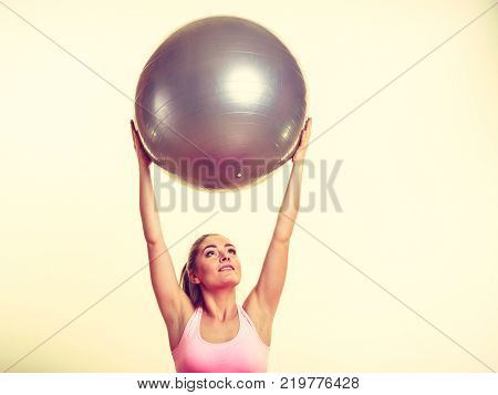 Girl with training equipment. Young female in gym with fit ball. Activity fitness health workout concept.