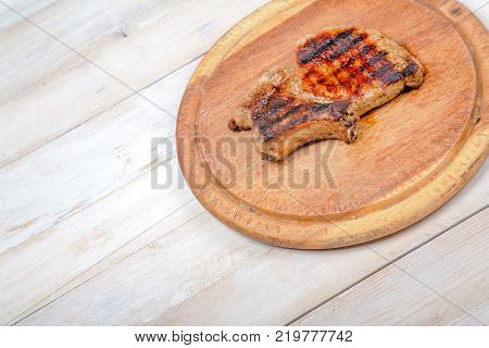 Grilled pork meat on wooden, round board