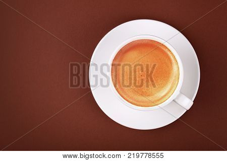 Close up white cup full of espresso coffee with crema froth on porcelain saucer over brown paper background close up elevated top view directly above