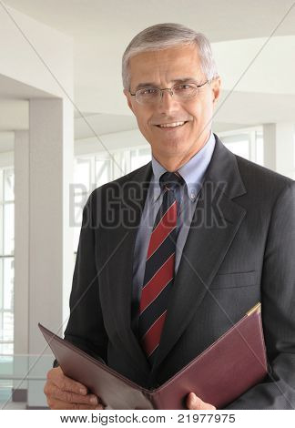 Portrait of a middle aged businessman in modern office building holding a leather portfolio. Vertical format with man smiling at camera.