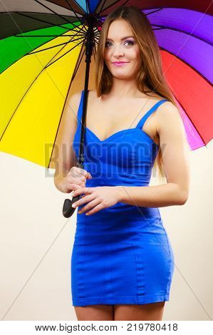 Woman fashion summer attractive girl wearing blue short dress standing under colorful rainbow umbrella on gray. Positive smiling female model. Forecasting and weather season concept