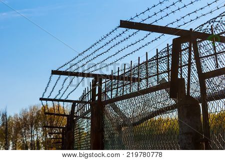 An iron fence with the barbed wire on the background of clear sky
