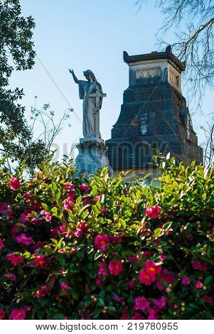 The sculpture of a woman with the cross the stone crypt and bushes of flowers on the Oakland Cemetery in sunny autumn day Atlanta USA