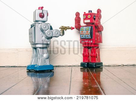 concept gun crime with retro toy robots on a wooden floor