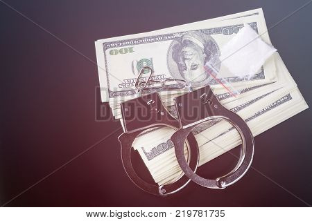 Handcuffs on stack of dollar banknotes and cocaine, black background