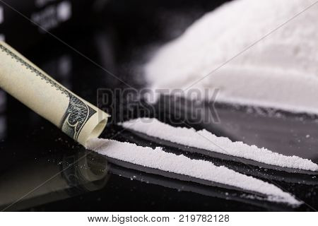 Cocaine on black background, close up.