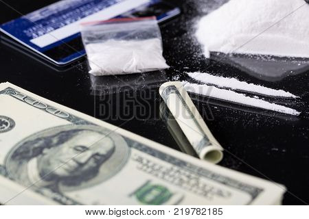 Rolled hundred dollars banknote, two lines and plastic packet of cocaine on black background, closeup