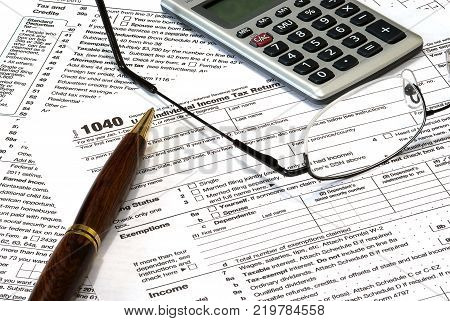A 1040 income tax form with a pen, calculator and glasses. The pen obscures the year to add to the image usefulness.