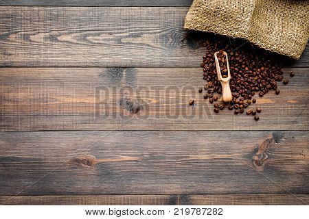 Coffee concept. Roasted beans in scoop near canvas on dark wooden background top view.