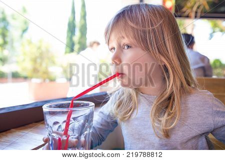 Child Drinking Water Through Red Straw Next To Window