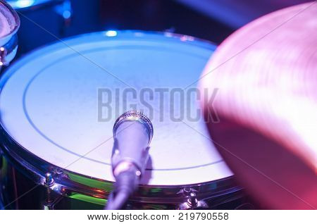 Snare is white with concert lighting and drum pozvonim microphone.