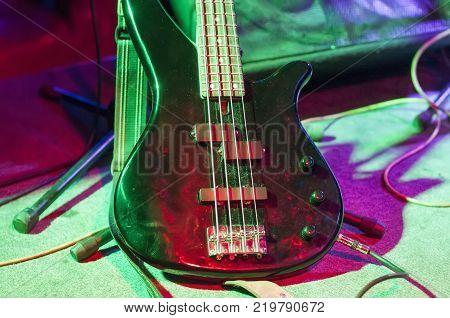 Guitar at the concert. Black bass guitar in Studio lighting.