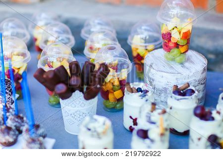 In photo depicts variety of goodies, delicious food, clear jars with cottage cheese souffl with layer of pastry topped with fruit and straws, chocolate long candy skewers in patterned white small vase, chocolate balls in coconut flakes with blue straw,
