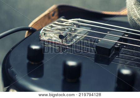 Electric bass guitar body and neck parts, pickup, on a black wooden background