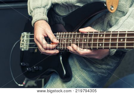 hands of bassist playing a micro bass guitar, blue image