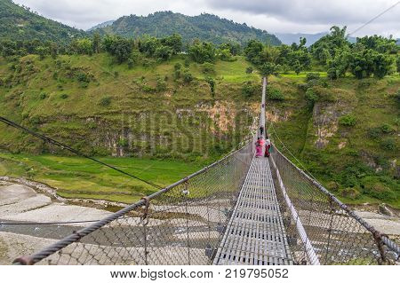 POKHARA NEPAL - October 01 2013: Unidentified people passing through a hanging bridge over the Seti river. Bridge connects two high banks outside of Pokhara in Nepal.