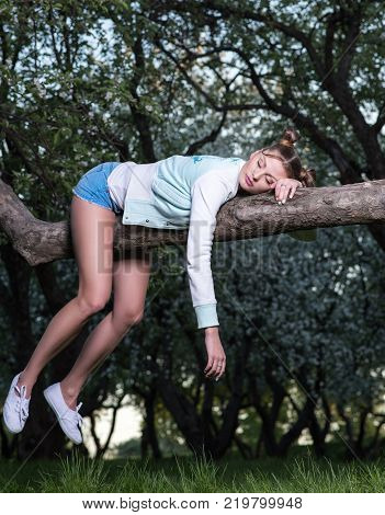 Evening fatigue in the garden. Young pretty woman sleeping tree legs dangling and one hand
